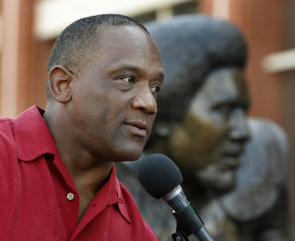 Photo -  Billy Sims speaks beside a statue of him unveiled before OU's game against North Texas on Sept. 1, 2017, in Norman. [Steve Sisney/The Oklahoman archives]