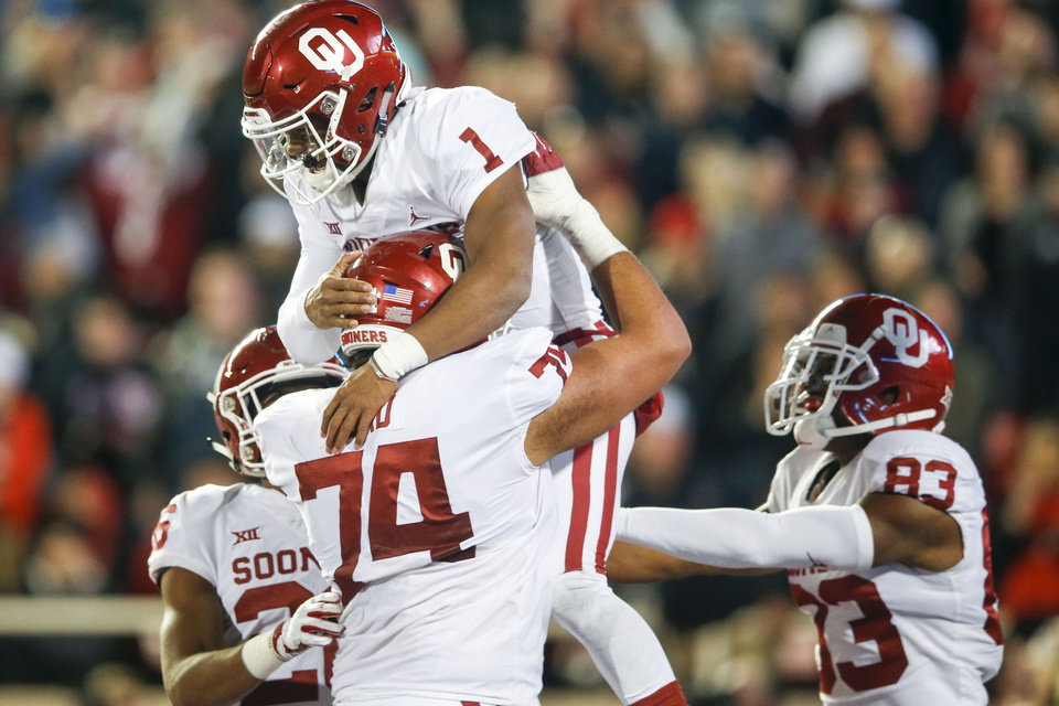 Photo - Oklahoma Sooners offensive lineman Cody Ford (74) lifts up Oklahoma Sooners quarterback Kyler Murray (1) after Murray's touchdown during the NCAA football game between the Texas Tech Red Raiders and the Oklahoma Sooners at Jones AT&T Stadium in Lubbock, Texas on Saturday, November 03, 2018. IAN MAULE/Tulsa World