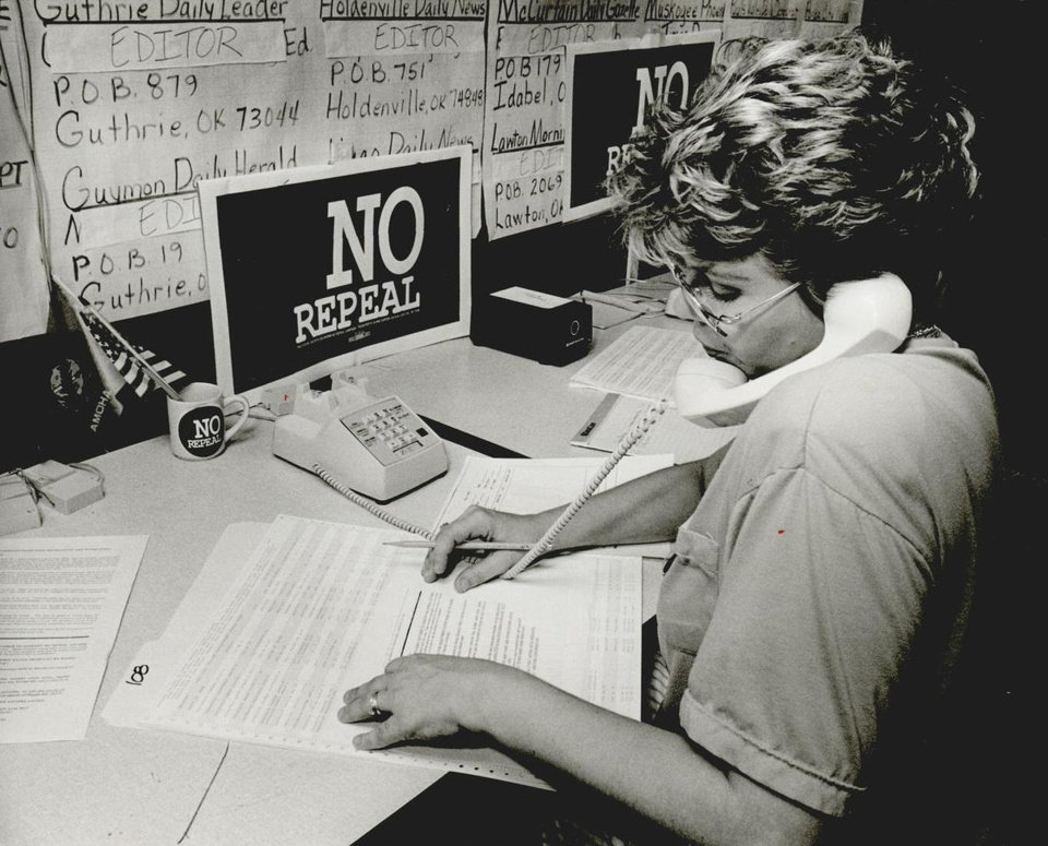 Photo - Supporter Cathy Davis is shown answering the telephone in September 1991 at the Oklahoma City headquarters of Growth Oklahoma, which was campaigning against the repeal of House Bill 1017. [Photo by Paul B. Southerland, The Oklahoman Archives]