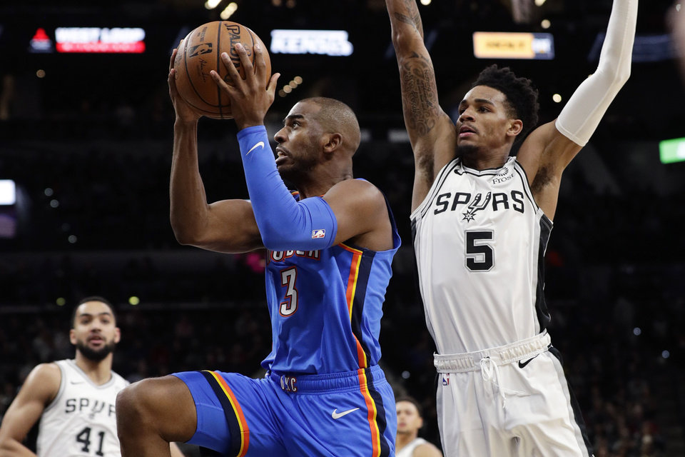 Photo - Oklahoma City Thunder guard Chris Paul (3) drives past San Antonio Spurs guard Dejounte Murray (5) during the first half of an NBA basketball game, in San Antonio, Thursday, Jan. 2, 2020. (AP Photo/Eric Gay)