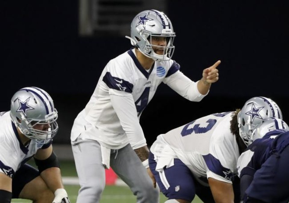 Photo -  Cowboys quarterback Dak Prescott (4) gives instructions at the line of scrimmage during drills Thursday in Frisco, Texas. [AP Photo/Tony Gutierrez]