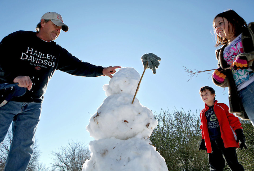 Photo - Gus Fritz, 6, and Faith Fritz, 9, watch Monday as their father, Freddie Fritz, puts penny eyes into a snowman outside the family's home in Shawnee. Cities around the Oklahoma City metro area continued Monday to recover from last week's winter storm. PHOTO BY JOHN CLANTON, THE OKLAHOMAN