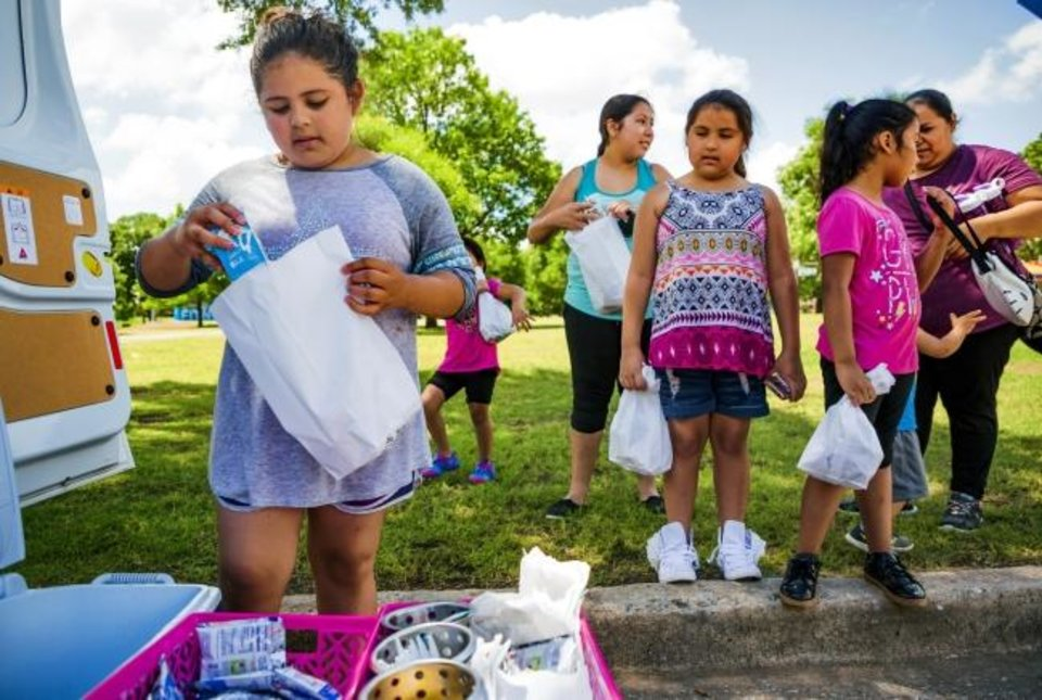 Photo -  Areli Uribe fills her lunch bag during the  Summer Feeding Program from Oklahoma City Public Schools at Wiley Post Park. [Chris Landsberger/The Oklahoman]