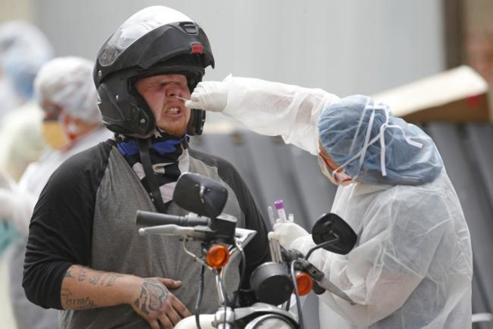 Photo -  A Community Health employee collects a sample with a swab from a man on a motorcycle at an April 7 drive-thru COVID-19 testing location outside Community Health Shawnee Family Medical Center in Shawnee. [Bryan Terry/The Oklahoman]