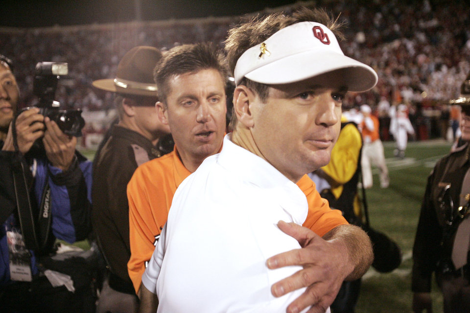 Photo - OSU head coach Mike Gundy congratulates OU head coach Bob Stoops after  the University of Oklahoma (OU Sooners) college football game against the Oklahoma State University (OSU Cowboys) at The Gaylord Family - Oklahoma Memorial Stadium Saturday, November 26, 2005 in Norman, Oklahoma. This is the 100th Bedlam football game. Doug Hoke /The Oklahoman