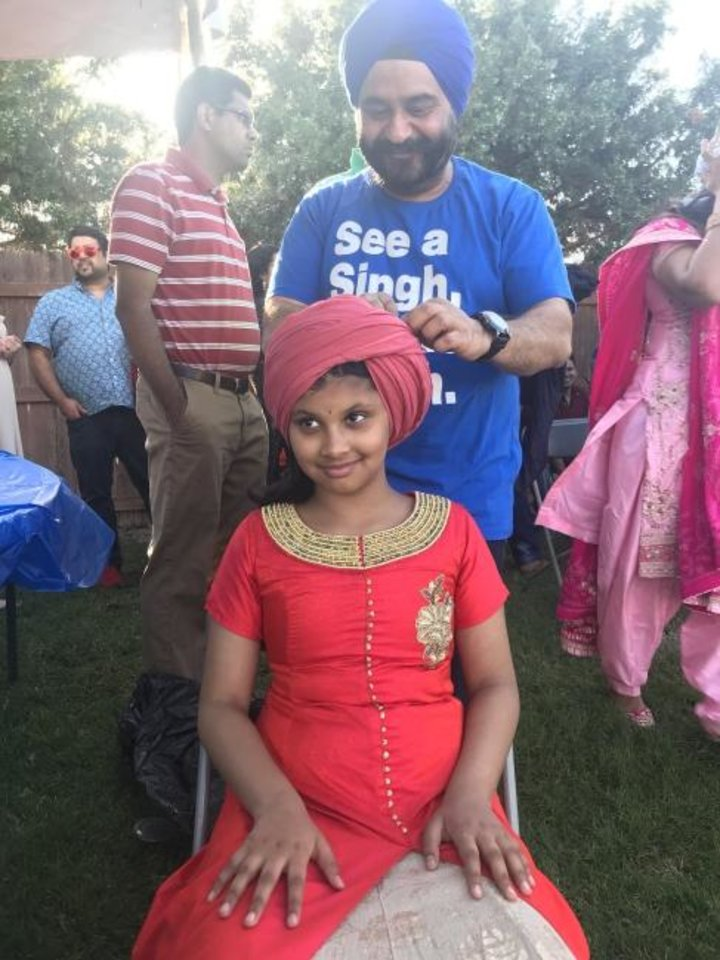 Photo -  Rhea Tulshan, a student at Lincoln Elementary School in Norman, sits as Hardeep Saluja ties a turban around her head during a turban tying demonstration at the Baisakhi Mela at the Sikh Gurdwara of Oklahoma, 4529 NW 16. [Carla Hinton/The Oklahoman]