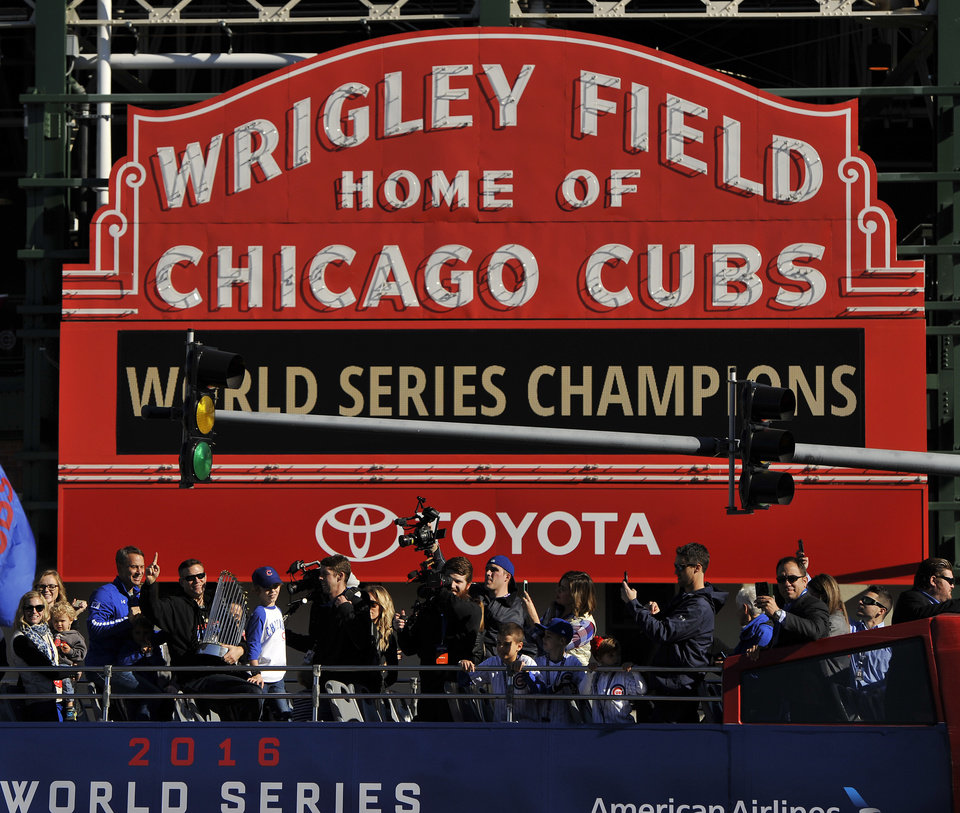 Photo - Chicago Cubs president of baseball operations Theo Epstein, gestures, at left, while holding the Commissioner's Trophy during a parade outside Wrigley Field honoring the World Series champions Friday, Nov. 4, 2016, in Chicago. (AP Photo/Paul Beaty)