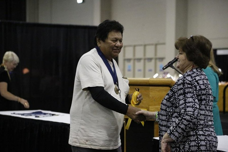 Photo - Lester Ortiz receives the Presidents Award from Red Earth Board President Lona Barrick during the 2019 Red Earth Festival at the Cox Convention Center in Oklahoma City, Oklahoma Friday, June 7, 2019. [Paxson Haws/The Oklahoman]