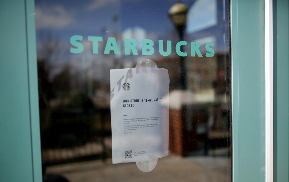 Photo - A sign on the door of Starbucks is pictured in Bricktown in Oklahoma City, Wednesday, March 18, 2020. [Sarah Phipps/The Oklahoman]
