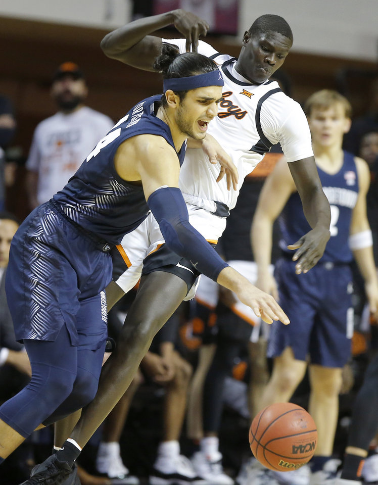 Photo - Georgetown's Omer Yurtseven (44) tries to get past Oklahoma State's Yor Anei (14) during a college basketball game between the Oklahoma State University Cowboys (OSU) and the Georgetown Hoyas at Gallagher-Iba Arena in Stillwater, Okla., Wednesday, Dec. 4, 2019. Georgetown won 84-71. [Bryan Terry/The Oklahoman]