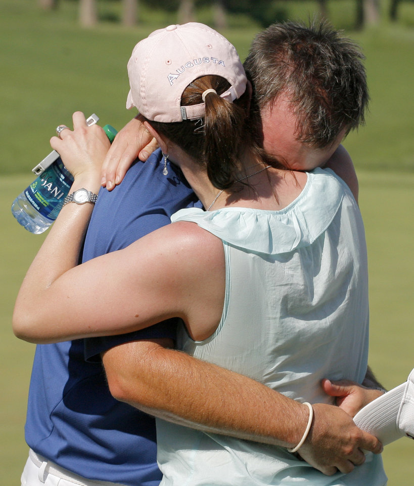 Photo - Augusta State head coach Josh Gregory hugs his wife Ashley Gregory after his team won the team match final of the NCAA Division I Men's Golf Championship at Karsten Creek Golf Course in Stillwater, Okla., Sunday, June 5, 2011.  Augusta State beat Georgia, 3-2. Photo by Nate Billings, The Oklahoman
