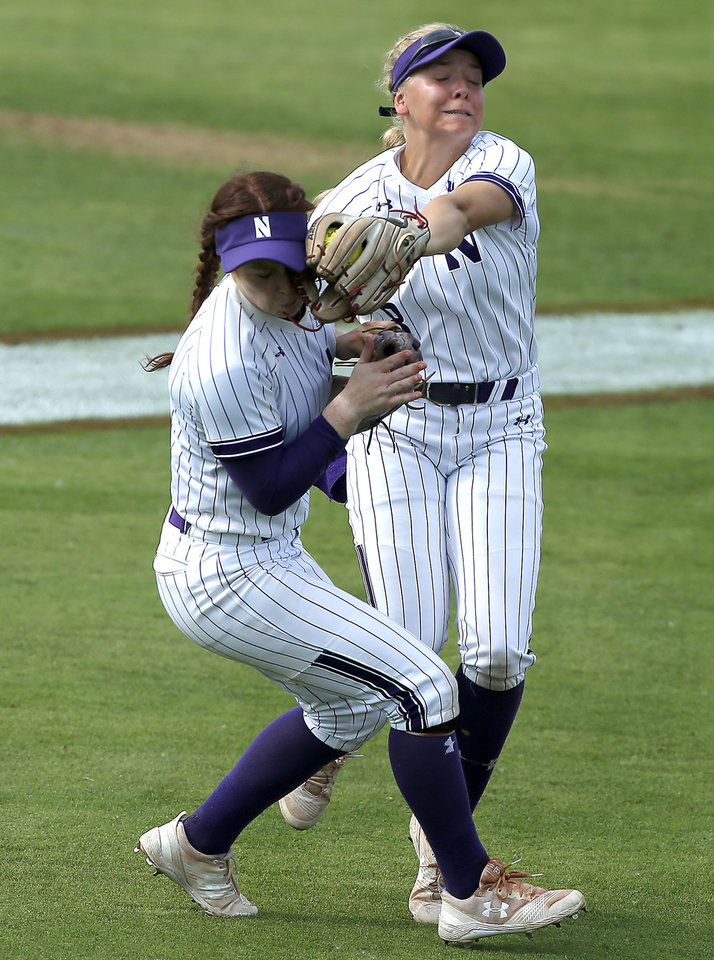 Photo - Northwestern's Skyler Shellmyer (8) catches the ball as she collides with Morgan Nelson (7) in the fifth inning of the second softball game in the Norman Super Regional between the University of Oklahoma (OU) and Northwestern in Norman, Okla., Saturday, May 25, 2019. Oklahoma won 8-0 to send them to the Women's College World Series. [Bryan Terry/The Oklahoman]