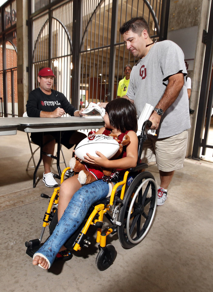 Photo - COLLEGE FOOTBALL / CHILD / CHILDREN / KIDS: Michael Turcotte, Houston, and daughter Gabbi, 6, get an autograph from head football coach Bob Stoops during fan appreciation day for the University of Oklahoma Sooner (OU) football team at Gaylord Family-Oklahoma Memorial Stadium in Norman, Okla., on Saturday, Aug. 3, 2013. Photo by Steve Sisney, The Oklahoman