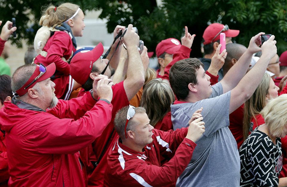 Photo - Oklahoma fans try to get a photo of the team bus as the Sooners arrive for the college football game between the University of Oklahoma Sooners (OU) and the University of Texas Longhorns (UT) during the Red River Showdown at the Cotton bowl in Dallas, Texas on Saturday, Oct. 11, 2014. Photo by Chris Landsberger, The Oklahoman