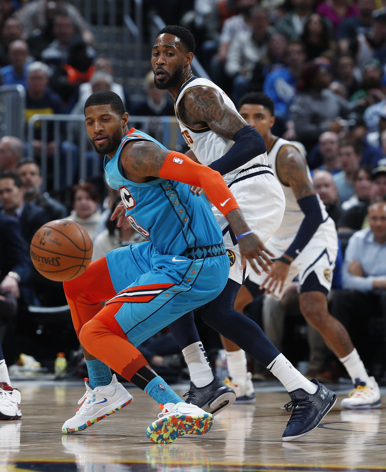 Photo - Oklahoma City Thunder forward Paul George, front, pursues a loose ball with Denver Nuggets guard Will Barton in the second half of an NBA basketball game Tuesday, Feb. 26, 2019, in Denver. The Nuggets won 121-112. (AP Photo/David Zalubowski)