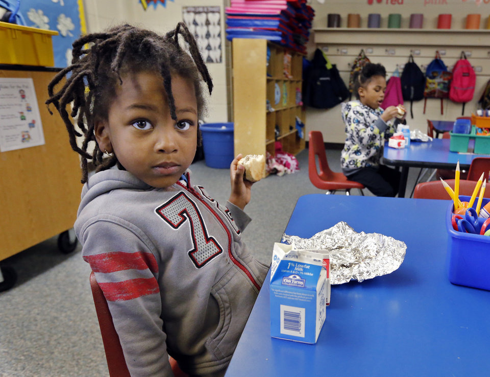 Photo -  Highland Park Elementary pre-k student Derrion Goins eats breakfast in Midwest City.