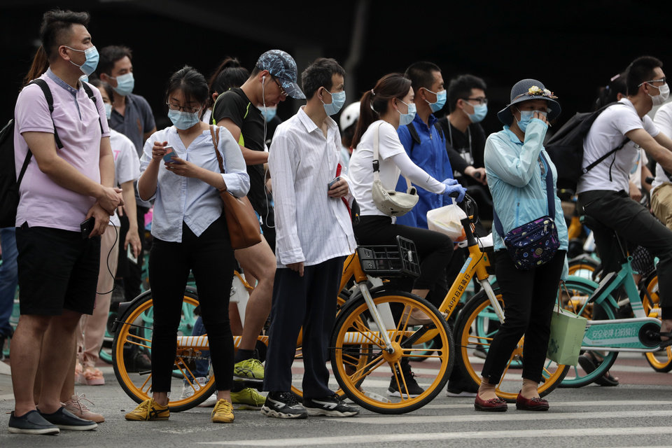 Photo -  People wearing protective face masks to help curb the spread of the coronavirus wait to cross a street in Beijing, on Monday. [Andy Wong/The Associated Press]