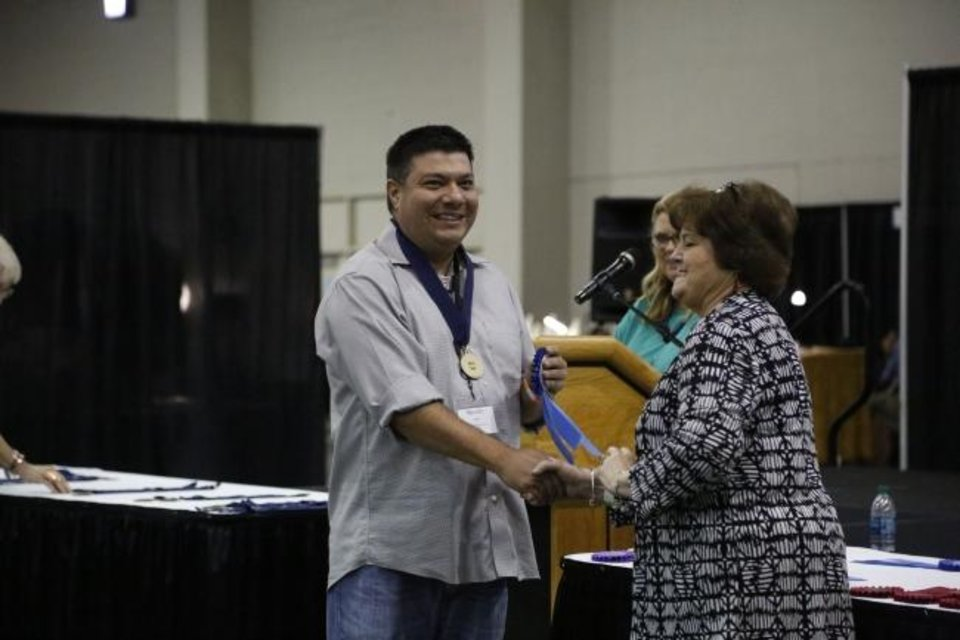 Photo -  Chase KahWinHut Earles receives his first-place ribbon for contemporary pottery from Red Earth Board President Lona Barrick during the 2019 Red Earth Festival at the Cox Convention Center in Oklahoma City, Oklahoma Friday, June 7, 2019.  [Paxson Haws/The Oklahoman]