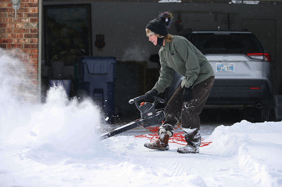 Photo - Vonnita Croy uses a leaf blower to clear her driveway in northwest Oklahoma City after a winter storm dropped another layer of snow in Oklahoma City, Wednesday, Feb. 17, 2021. [Bryan Terry/The Oklahoman]