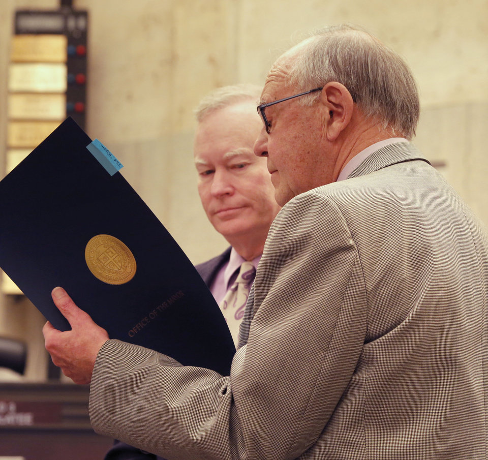 Photo -  Oklahoma City Mayor Mick Cornett, left, and Ward 8 Councilman Pat Ryan read a proclamation on the final day of Ryan's 10 years in the position, during the Oklahoma City Council meeting in Oklahoma City Tuesday, April 7, 2015, Photo by Paul Hellstern, The Oklahoman   PAUL HELLSTERN -  Oklahoman