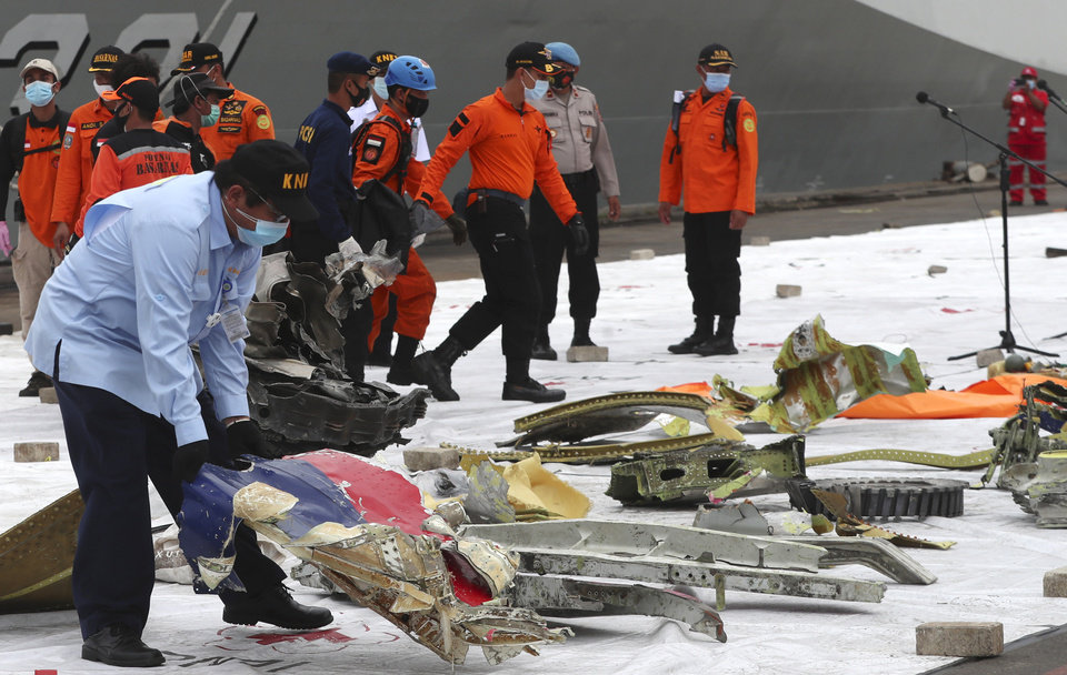 Photo -  An Indonesian National Transportation Safety Committee (KNKT) investigator inspects the debris found in the waters around the location where Sriwijaya Air passenger jet crashed at Tanjung Priok Port in Jakarta, Indonesia, Monday, Jan. 11, 2021. The search for the black boxes of a crashed Sriwijaya Air jet has intensified to boost the investigation into what caused the plane carrying dozens of people to nosedive into Indonesia seas. The Boeing 737-500 jet disappeared during heavy rain on Saturday.  (AP Photo/Achmad Ibrahim)