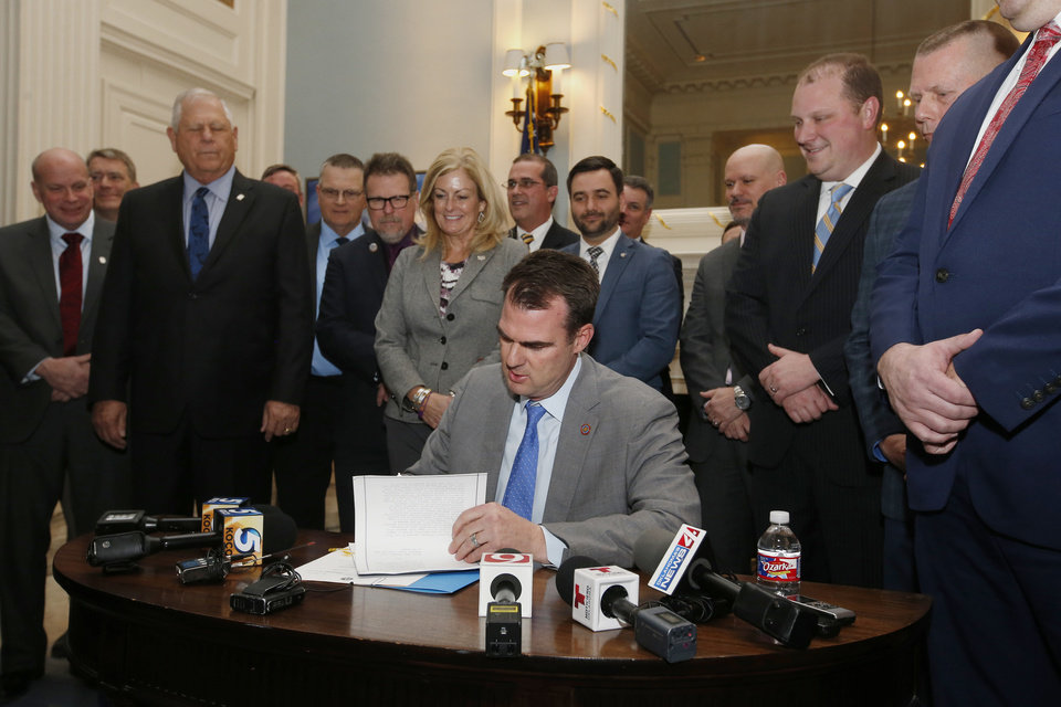 Photo - Oklahoma Gov. Kevin Stitt signs the permitless carry bill into law, as legislators look on,  Wednesday, Feb. 27, 2019, in Oklahoma City. (AP Photo/Sue Ogrocki)