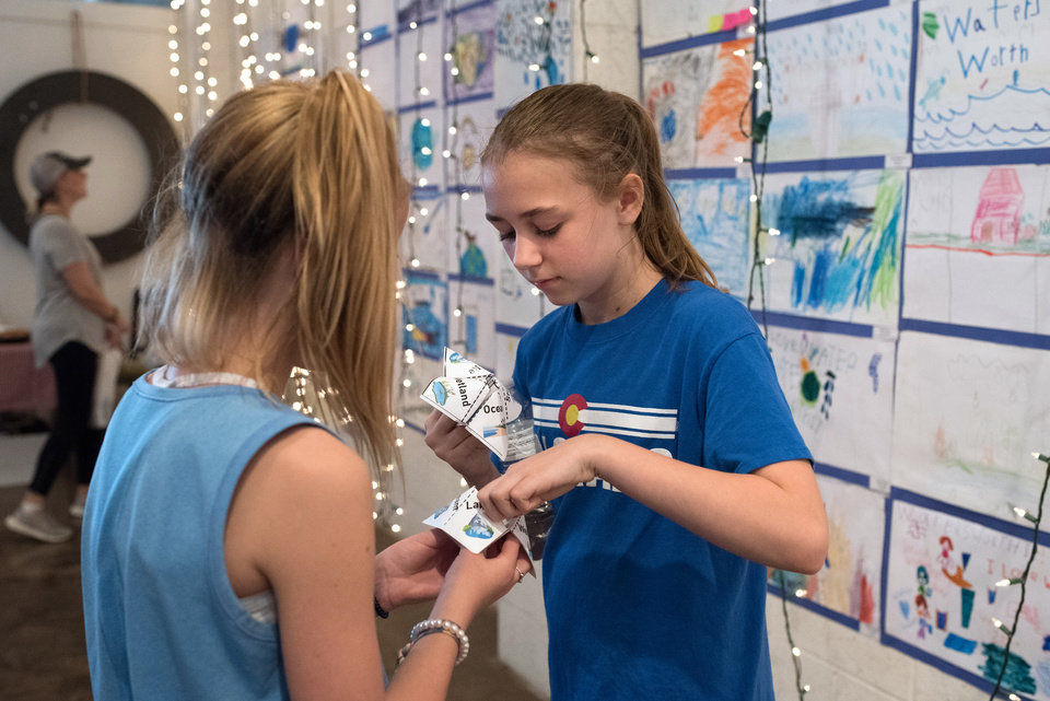 Photo -  Abby Kornele, 11, right, and Sadie Stover, 11, use a fortuneteller at the 2018 Water's Worth It art show put on by the city of Norman Environmental Control Advisory Board. [PHOTO BY WHITNEY BRYEN, FOR THE OKLAHOMAN]