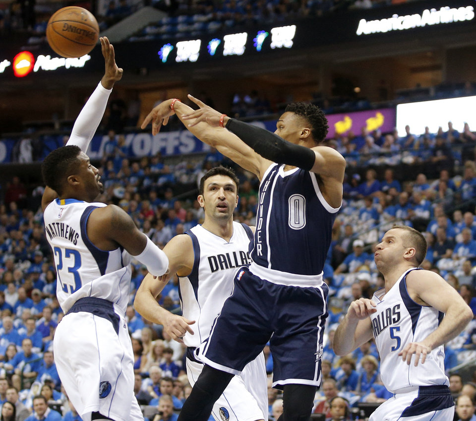 Photo - Oklahoma City's Russell Westbrook (0) passes the ball as Dallas' Wesley Matthews (23), Zaza Pachulia (27) and J.J. Barea (5) defend during Game 3 of the first round series between the Oklahoma City Thunder and the Dallas Mavericks in the NBA playoffs at American Airlines Center in Dallas, Thursday, April 21, 2016. The Thunder won 131-102. Photo by Bryan Terry, The Oklahoman