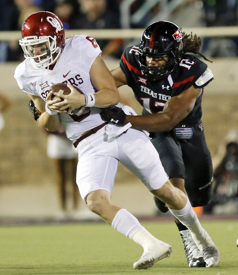 Photo - Oklahoma's Baker Mayfield (6) scrambles away from Texas Tech's Zach Barnes (12) in the first quarter during a college football game between the University of Oklahoma Sooners (OU) and Texas Tech Red Raiders at Jones AT&T Stadium in Lubbock, Texas, Saturday, Oct. 22, 2016. Photo by Nate Billings, The Oklahoman