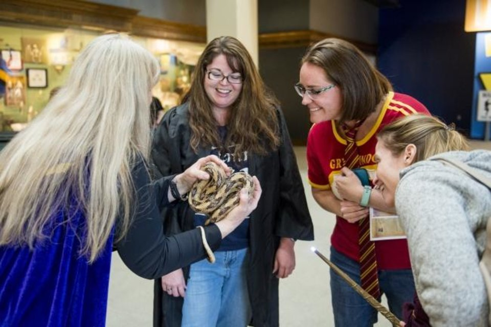 Photo -  Attendees examine a snake during a wizard-themed SMO 21 event for grown-ups April 20, 2018, at Science Museum Oklahoma. [Provided]