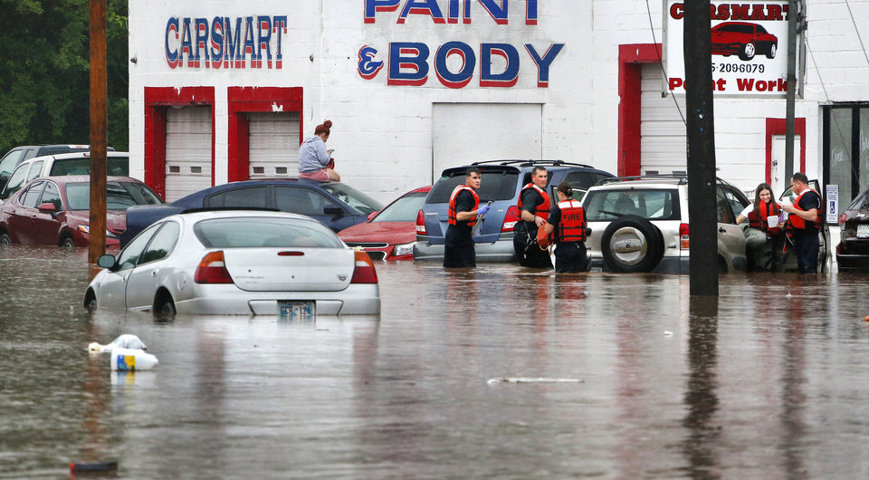 Photo - A firefighter helps a woman out of a car, far right,  after giving her a flotation vest as another woman sits atop her car, left, waiting to be rescued when heavy rains overwhelmed stormwater drainage systems and caused flooded streets, requiring  high water rescues in Oklahoma City as another round of severe storms passes through the metro.