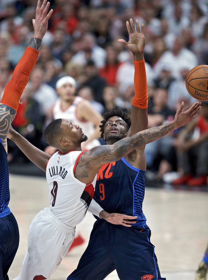 Photo - Portland Trail Blazers guard Damian Lillard, left, shoots by Oklahoma City Thunder forward Jerami Grant during the first half of Game 5 of an NBA basketball first-round playoff series, Tuesday, April 23, 2019, in Portland, Ore. (AP Photo/Craig Mitchelldyer)