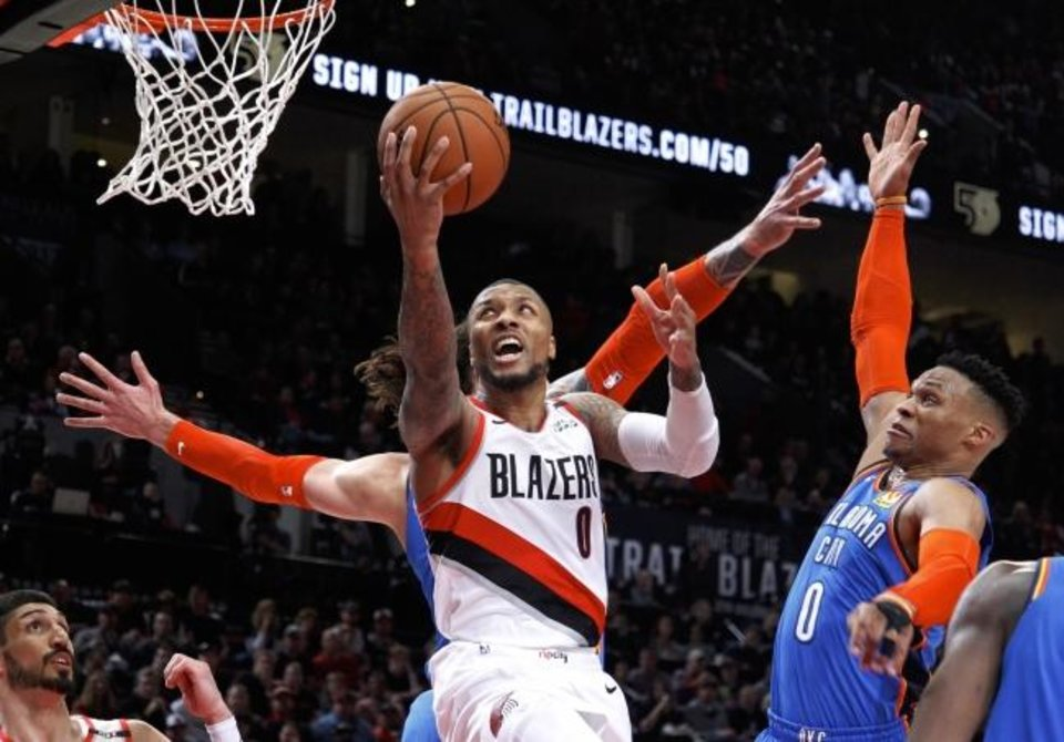 Photo -  Portland's Damian Lillard drives to the basket past Oklahoma City's Russell Westbrook during Game 1 of their series Sunday in Portland. [AP Photo]