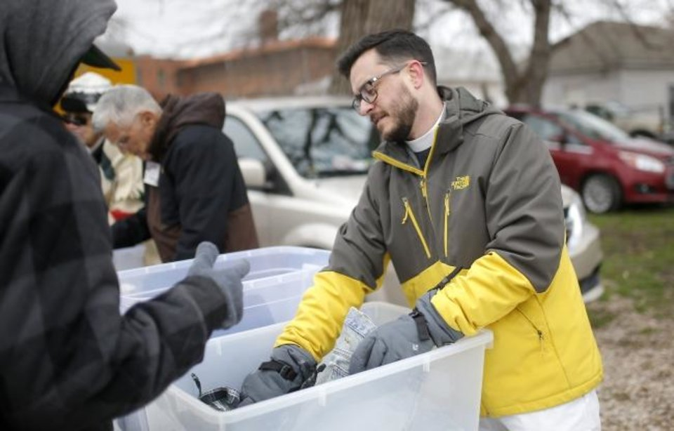 Photo -  The Rev. Tim Baer, rector of Grace Episcopal Church in Yukon, hands out clothing to those in need during the weekly Ice Angels ministry outreach in south Oklahoma City. [Sarah Phipps/The Oklahoman]