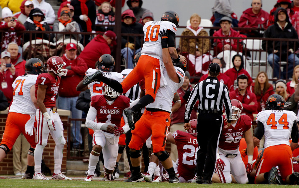 Photo - Cowboy's Michael Wilson (74) lifts quarterback Mason Rudolph (10) in the air after a touchdown pass during a Bedlam college football game between the University of Oklahoma Sooners (OU) and the Oklahoma State Cowboys (OSU) at Gaylord Family-Oklahoma Memorial Stadium in Norman, Okla., on Saturday, Dec. 6, 2014. Photo by Steve Sisney, The Oklahoman
