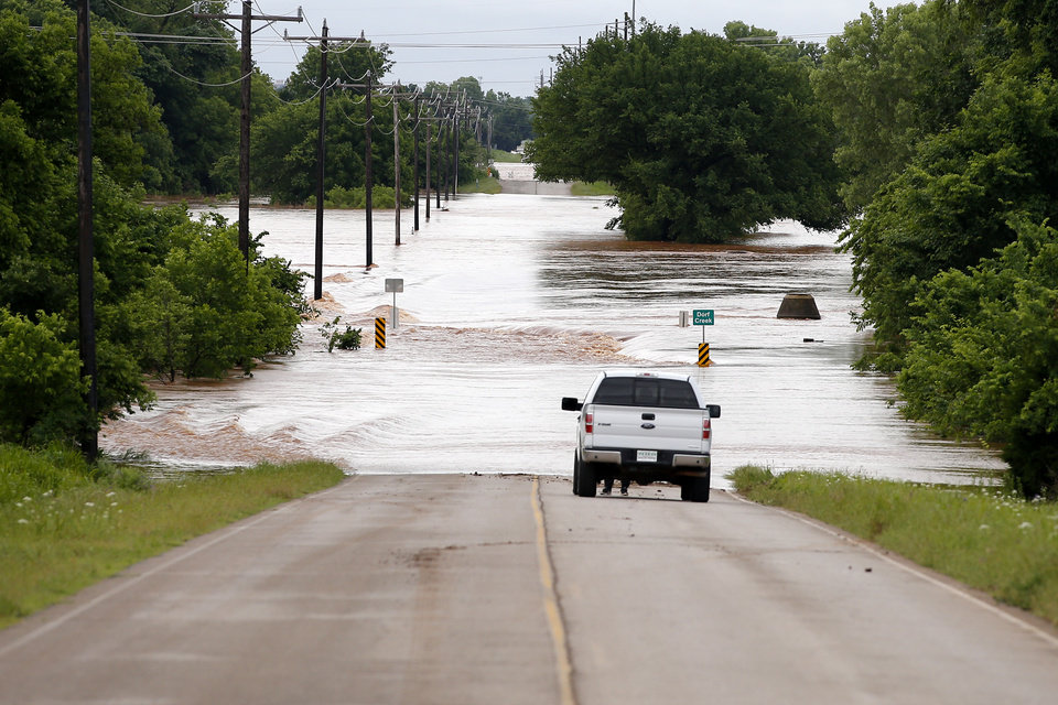 Photo - Water flows over Meridian just north of NW 206 in Oklahoma City, Tuesday, May 21, 2019. [Bryan Terry/The Oklahoman]