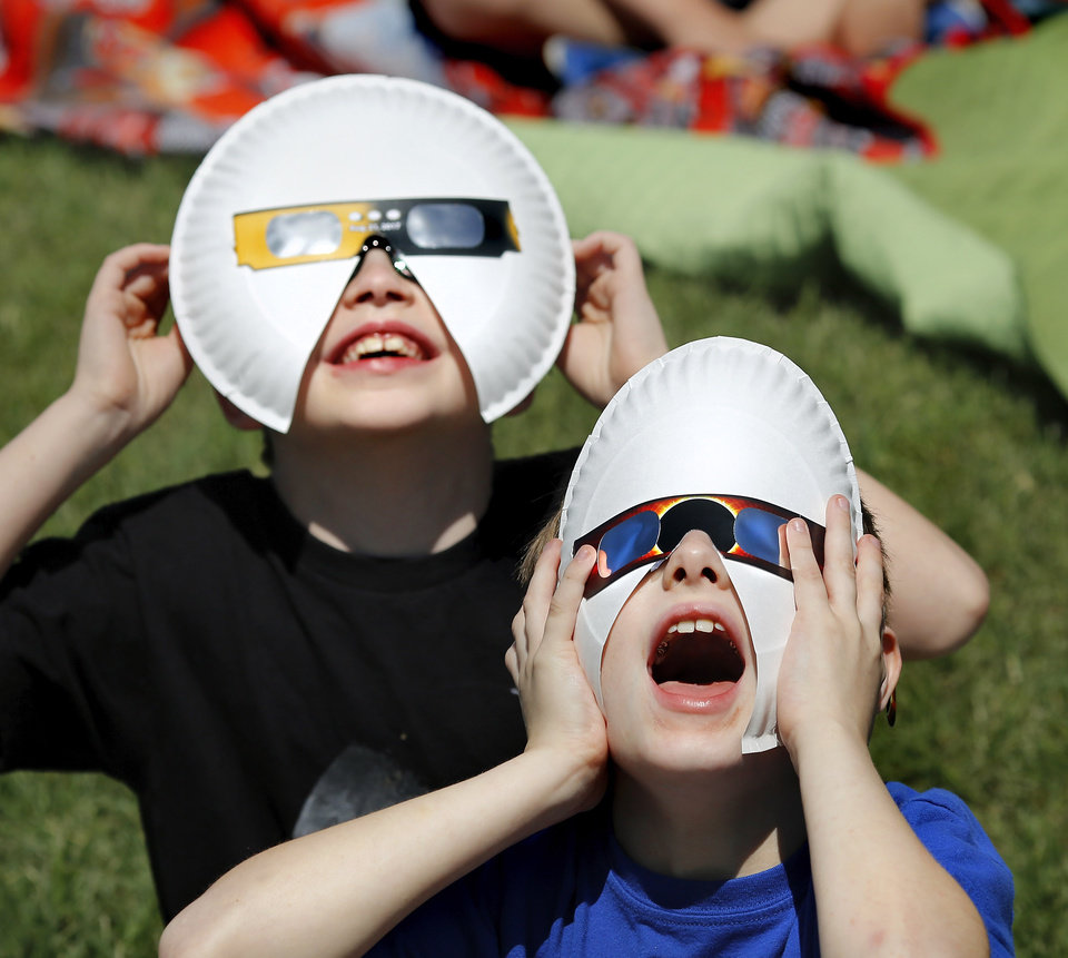 Photo -  Austin Taylor, front, and Brendan Hampton wear customized viewing glasses to get a safe look at the eclipse. The entire student body, faculty and some parents gathered in a field on the north side of James Griffith Intermediate School to view the solar eclipse Monday afternoon. [Photo by Jim Beckel, The Oklahoman]