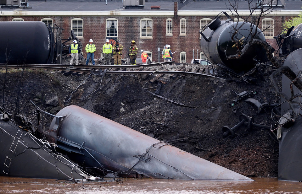 Photo -  Firefighters and rescue personnel work Wednesday along the tracks where several tanker cars carrying crude oil derailed and caught fire along the James River in Lynchburg, Va.  AP Photo   Parker Michels-Boyce -  AP