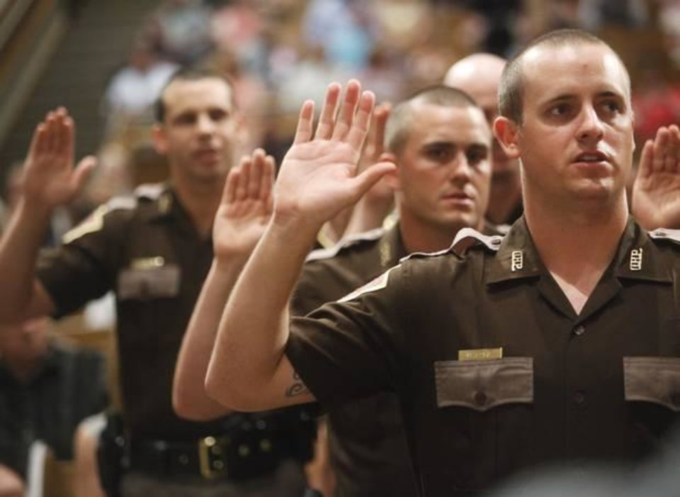 Photo - Officer Dalas Anderson swears the oath of office during the 62nd Oklahoma Highway Patrol graduation at the Memorial Road Church of Christ in Edmond on June 13, 2014. Photo by KT King/The Oklahoman