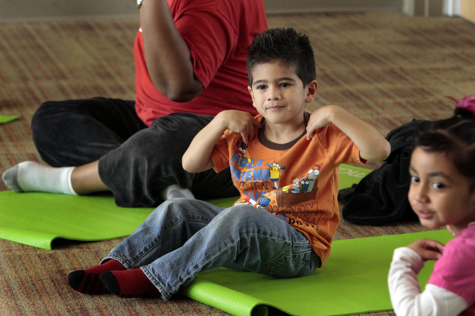 Photo - Aaron Secondino works out as Angela Moorad teaches yoga to three and four-year-olds on Wednesday, March 7, 2012, in Oklahoma City, Okla.  Photo by Steve Sisney, The Oklahoman