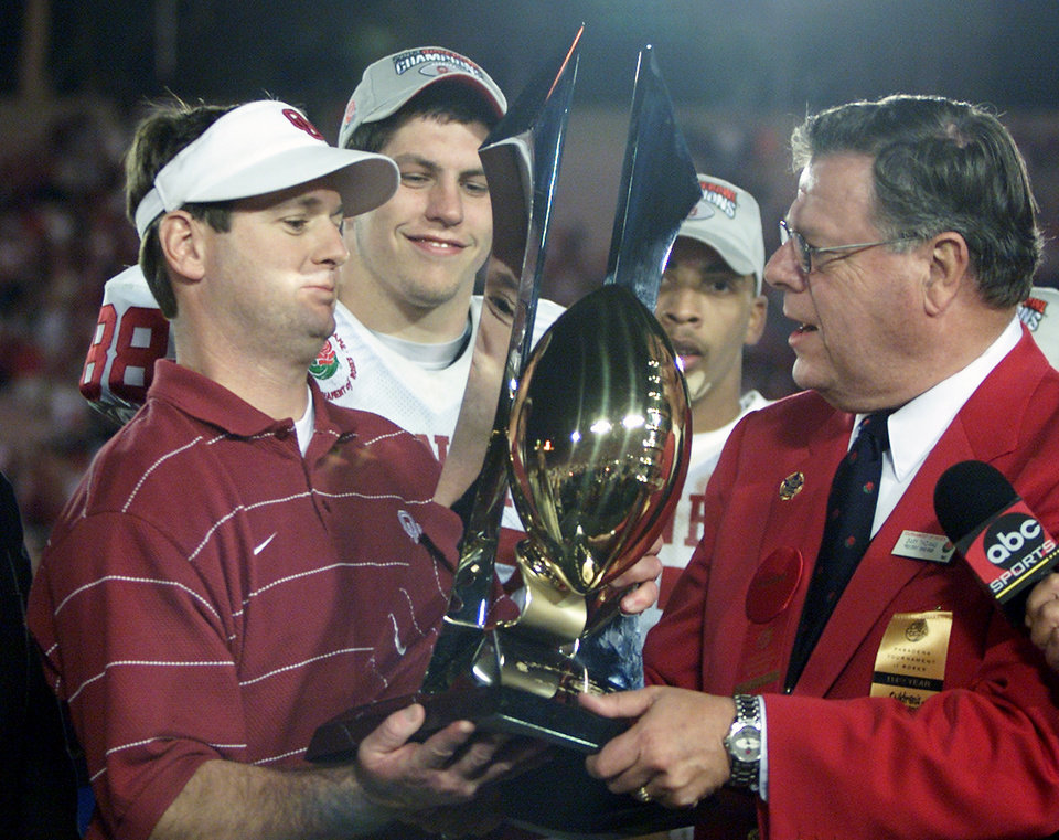 Photo - University of Oklahoma college football against Washington State University at the Rose Bowl in Pasadena, CA on Jan. 1, 2003. OU head coach Bob Stoops is presented the Rose Bowl trophy. Behind is Trent Smith and Andre Woolfolk.   Staff photo by Doug Hoke