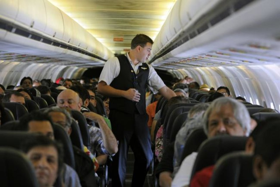 Photo -  Allegiant Air flight attendant Chris Killian prepares his passengers for the Laredo, Texas-bound flight before it pushes back from the terminal at McCarran International Airport in Las Vegas. [AP PHOTO]
