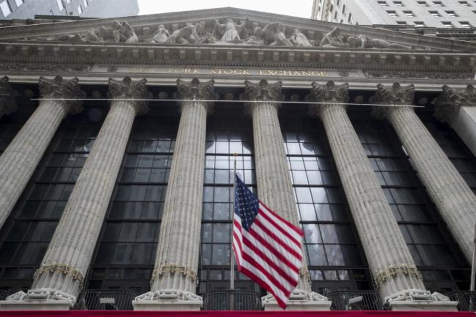 Photo -  A U.S.  flag flies outside New York Stock Exchange.  [AP PHOTO]