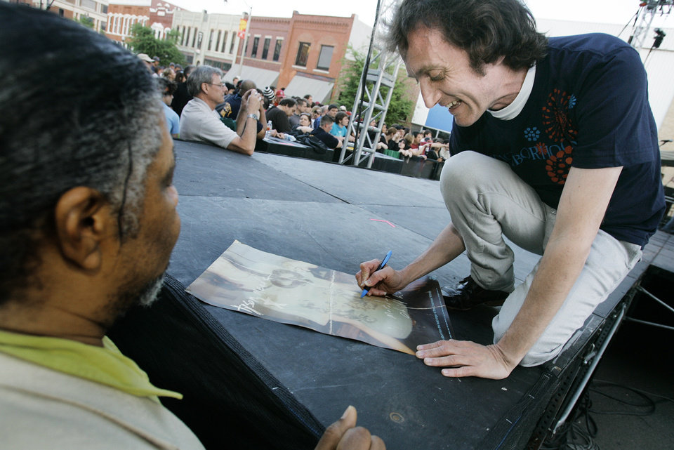 Photo -  Chainsaw Kittens lead singer Tyson Meade signs an autograph in 2008 for Ricardo Morrison of Norman before performing at the Norman Music Festival. [The Oklahoman Archives]