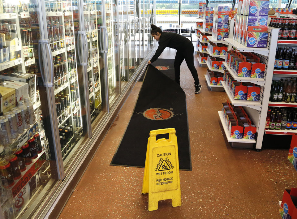Photo - Pops store employee Klarissa Fraire lays down a mat over a wet floor where bottles fell and shattered at  the Pops store in Arcadia, OK after an early morning 5.6 magnitude earthquake struck near Pawnee, Okla. Saturday, Sept. 3, 2016.  Photo by Paul Hellstern, The Oklahoman