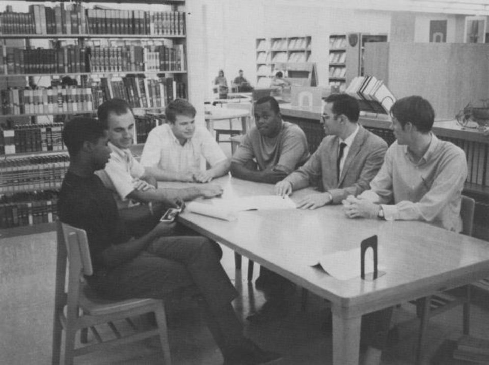 Photo -  In this Oklahoma Christian College yearbook photo, Ron Wright, middle, is one of two black students shown talking with white students in the college's library. [Photo provided]
