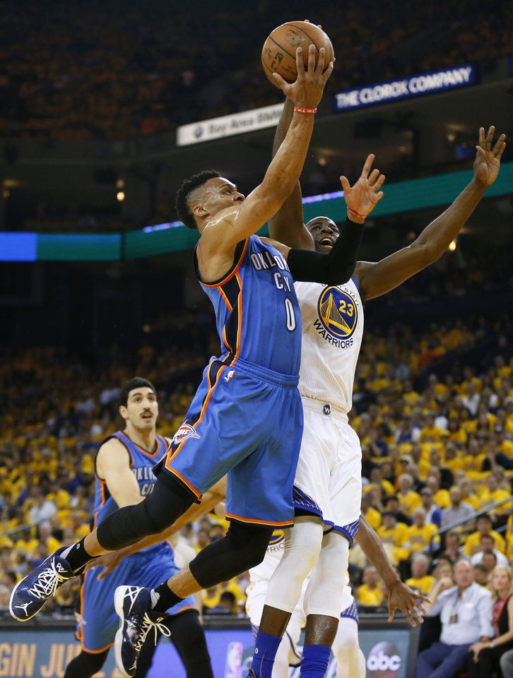 Photo - Oklahoma City's Russell Westbrook (0) goes past Golden State's Draymond Green (23) during Game 2 of the Western Conference finals in the NBA playoffs between the Oklahoma City Thunder and the Golden State Warriors at Oracle Arena in Oakland, Calif., Wednesday, May 18, 2016. Photo by Nate Billings, The Oklahoman