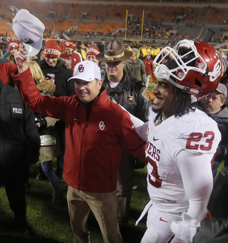 Photo - OU coach Bob Stoops holds a Big 12 Championship hat as he celebrates with Devante Bond (23) after the Bedlam college football game between the Oklahoma State Cowboys (OSU) and the University of Oklahoma Sooners (OU) at Boone Pickens Stadium in Stillwater, Okla., Saturday, Nov. 28, 2015. OU won 58-23. Photo by Nate Billings, The Oklahoman