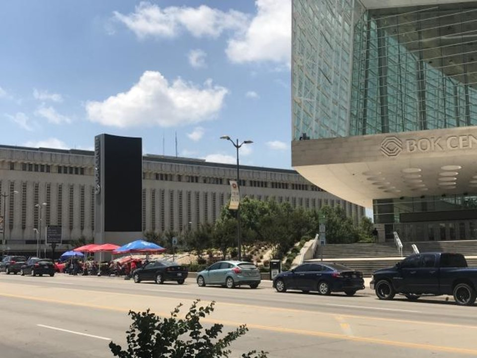 Photo -  People in line to get into the campaign rally for President Donald Trump sit under umbrellas and tents on Wednesday outside the BOK Center in downtown Tulsa. [Carla Hinton/The Oklahoman]