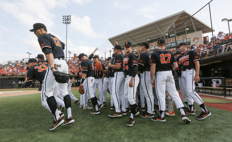 Photo - The OSU Cowboys break their huddle to take the field at the start of a college baseball game between Baylor and Oklahoma State in the last regular-season series at Allie P. Reynolds Stadium in Stillwater, Okla., Friday, May 17, 2019. [Nate Billings/The Oklahoman]